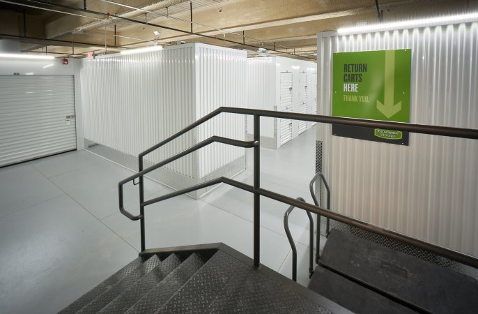 Stairs leading to white storage lockers in indoor storage facility